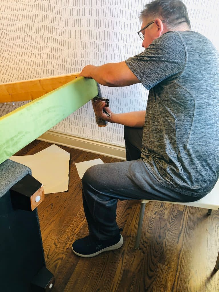 In order to reupholster, Geraint is recovering the existing frame with green velvet-like fabric starting with the legs and sides of the bed frame.