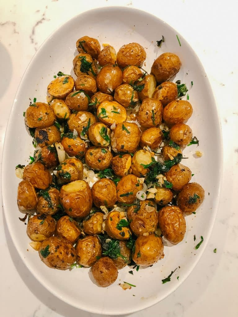 Delicious roasted potatoes with garlic and Spanish onions from the garden and the savoury herb combination added