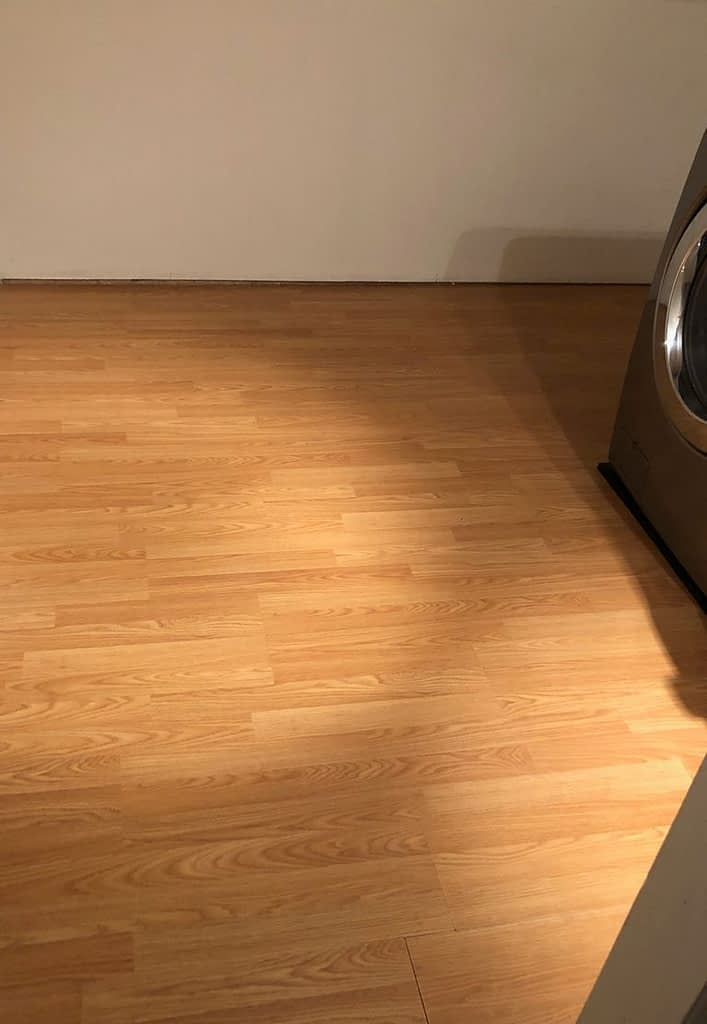 Before: Orange-tone laminate laundry room floor