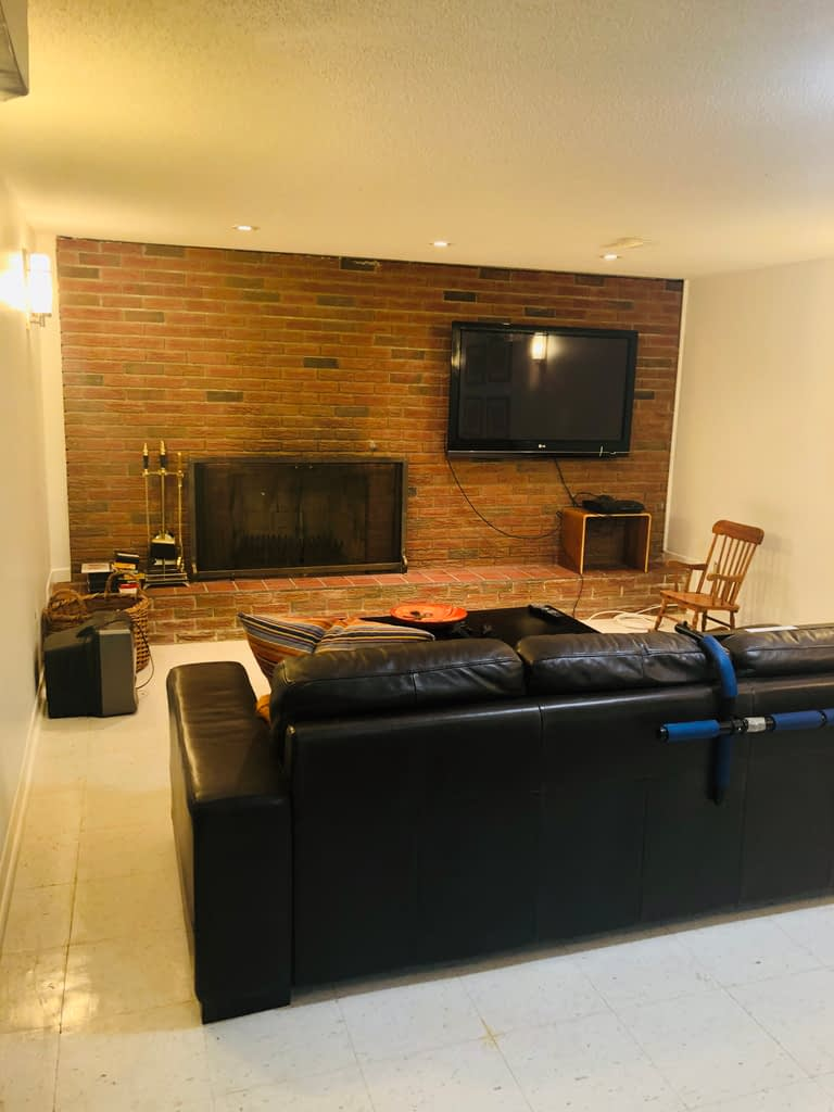 Here is a shot of our original 1970s basement.  This fireplace will be painted and we have to address the wire management situation.