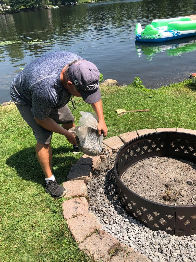 Ger adding the crushed stone around the fire pit.