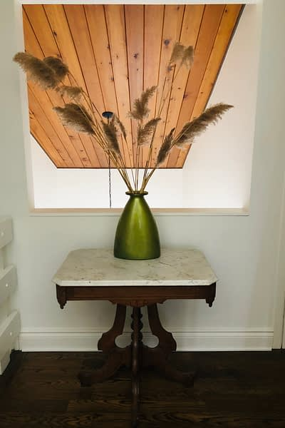 An antique table with a modern vase